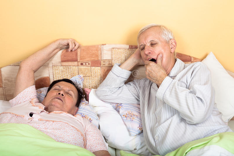 困资深夫妇在床上 库存图片