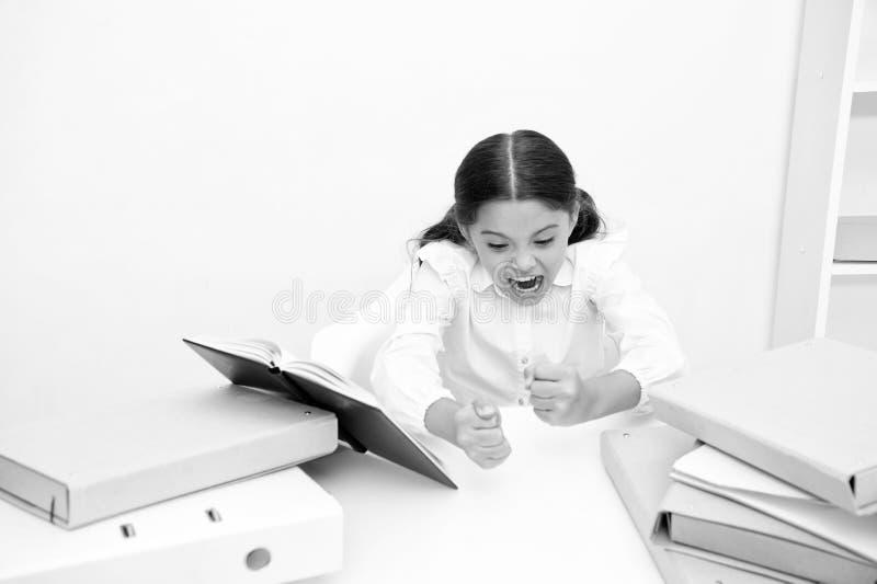 困难学习 当坐桌白色背景时,女孩孩子读书 学习的女小学生和阅读书 孩子学校 免版税库存照片