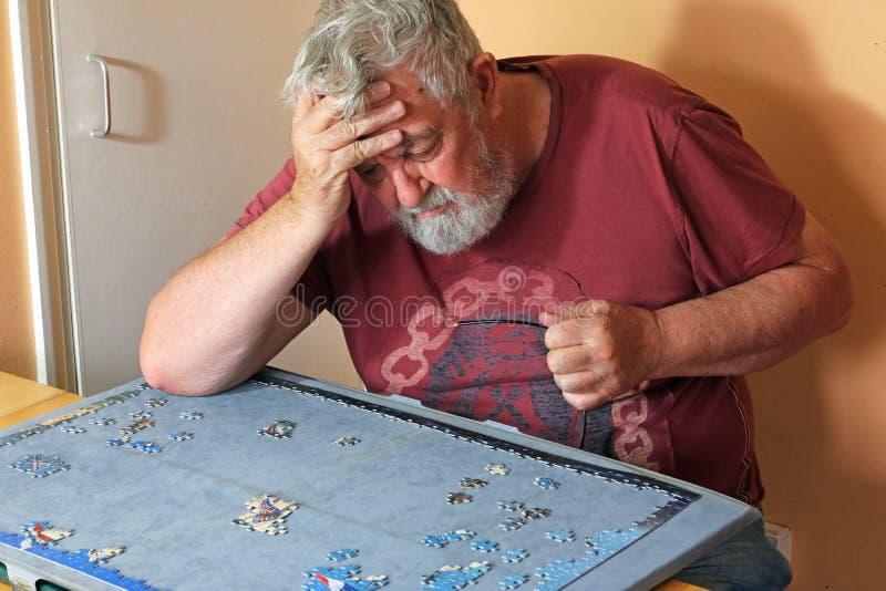 困难的老人独自地做一个七巧板 图库摄影