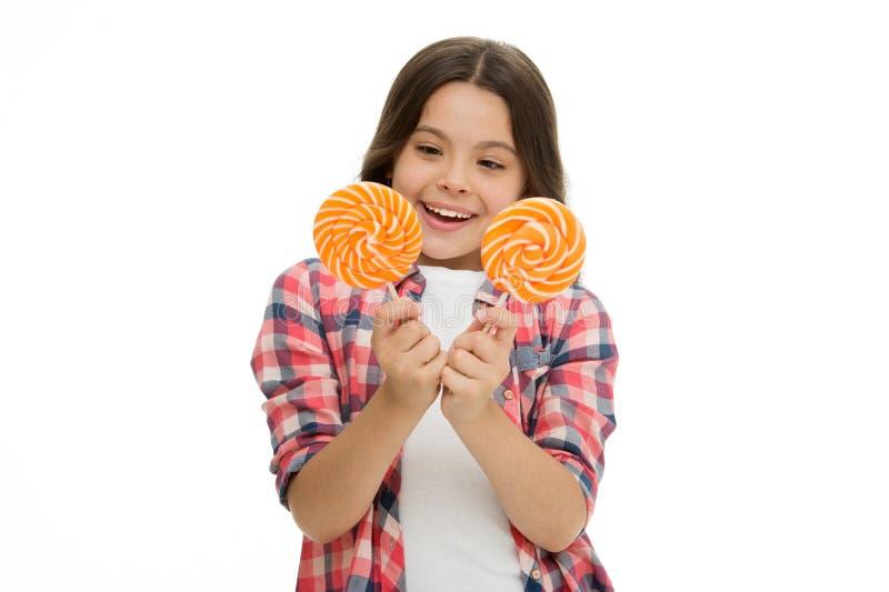 困难的选择 女孩举行两棒棒糖在白色的手上 女孩不可能决定哪个棒棒糖她想要 甜点 免版税图库摄影