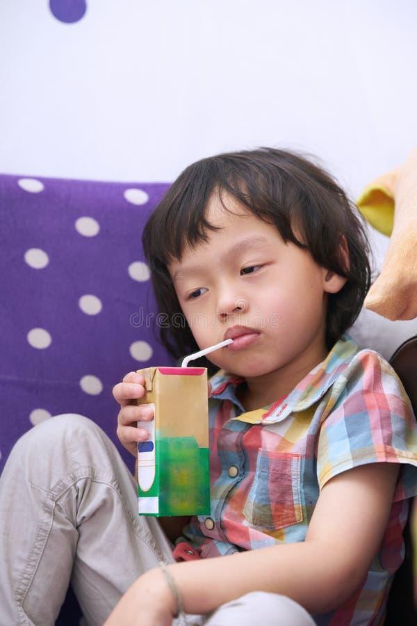 困面孔男孩坐和乏味喝在握手的牛奶 免版税库存照片