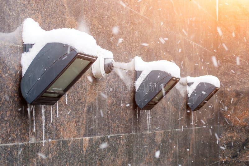 围住用与冰柱的雪盖的照明设备灯笼从冰和一台摄象机 库存照片