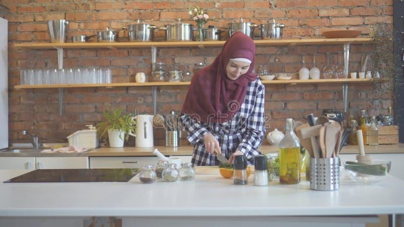 围巾的俏丽的回教年轻女人在厨房里准备 免版税图库摄影