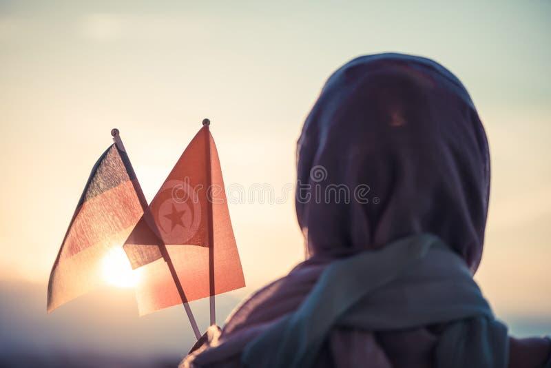 围巾的回教妇女有在日落突尼斯和德国旗子的  ?? 免版税库存照片