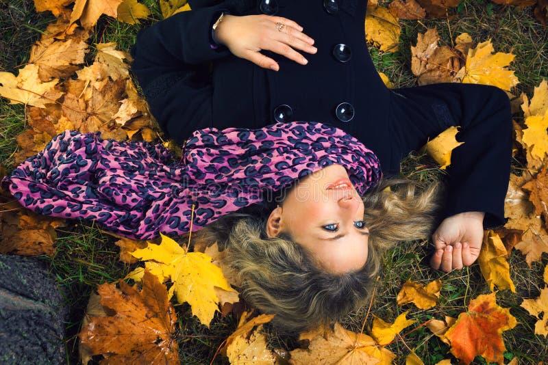 围巾的美丽的女孩在秋天结构树下 免版税库存图片