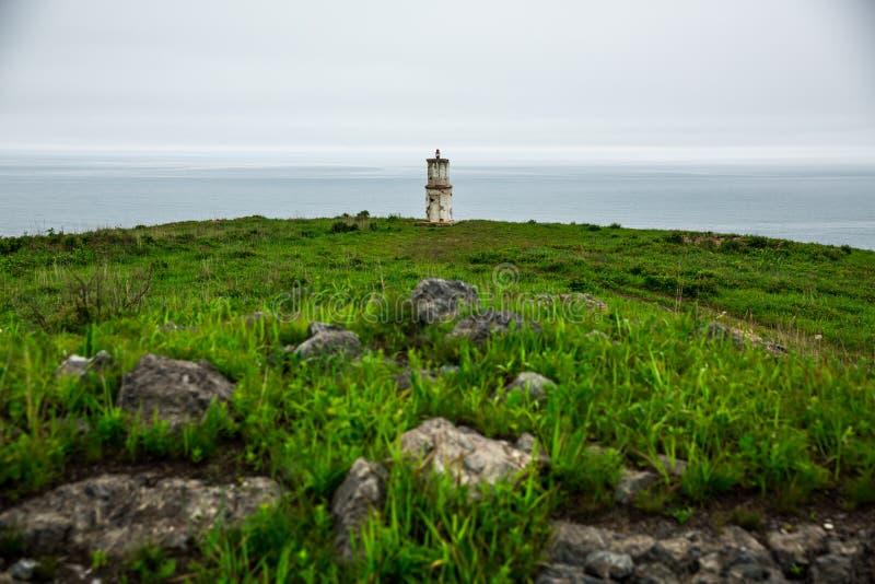 围绕海的背景灯塔多云天气的 库存图片