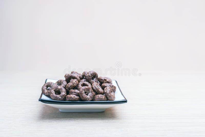 围绕燕麦的嘎吱咬嚼的整个五谷巧克力谷物在轻的木表上的一个方形的盘 健康有机快餐,食物,早餐 免版税库存图片
