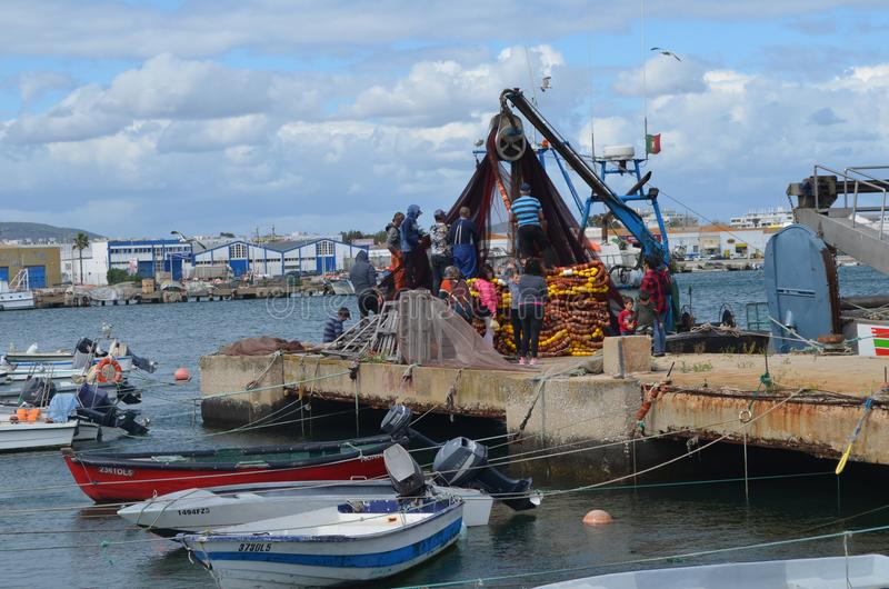 围网渔船的乘员组在Olhao钓鱼海港,阿尔加威,南葡萄牙收集它的网 图库摄影