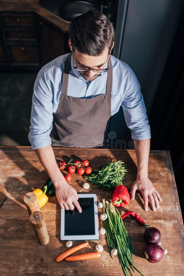围裙烹调的英俊的年轻人 免版税库存图片
