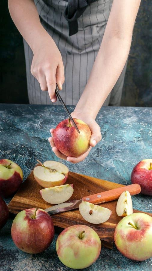 围裙的一个女孩切开一把刀子用在一个切板的成熟苹果 蓝色具体背景 免版税图库摄影
