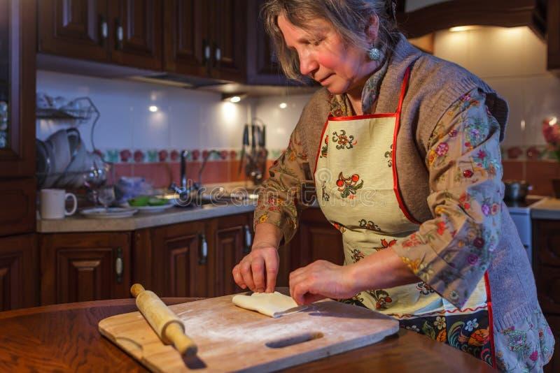 围裙的一名年长妇女准备饼 图库摄影