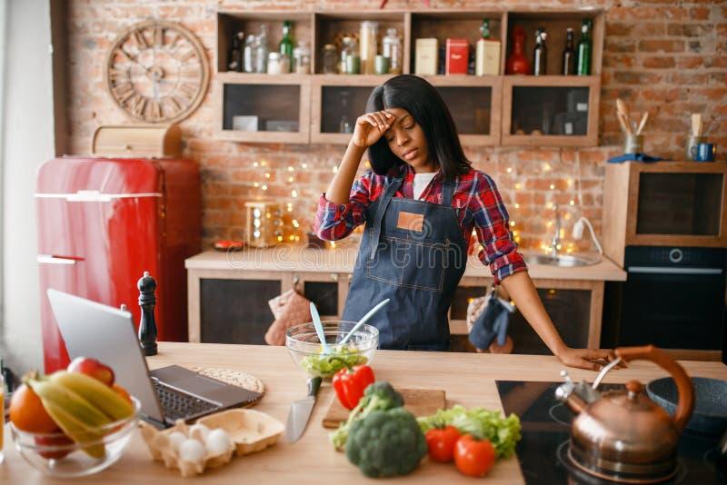 围裙的困黑人妇女烹调在厨房的 免版税库存照片