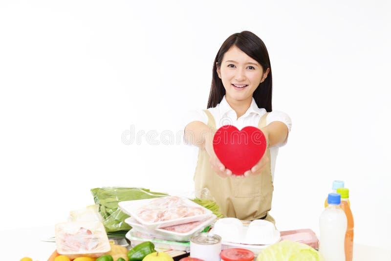 围裙的妇女与粮食 库存照片