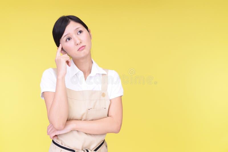 围裙的心神不安的亚裔妇女 免版税库存图片