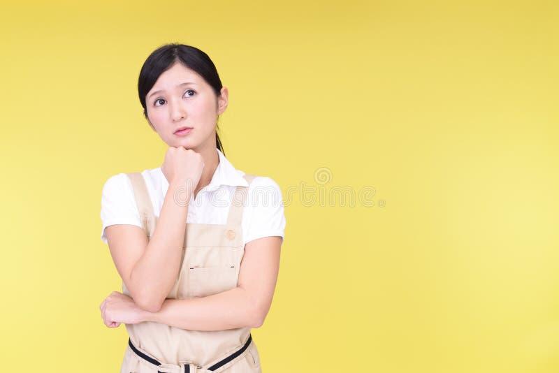 围裙的心神不安的亚裔妇女 库存图片