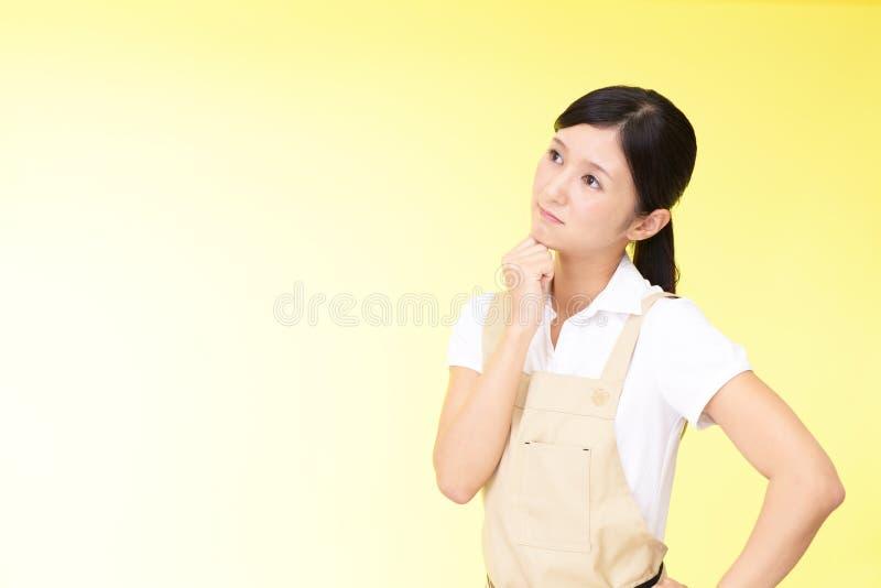 围裙的心神不安的亚裔妇女 免版税图库摄影