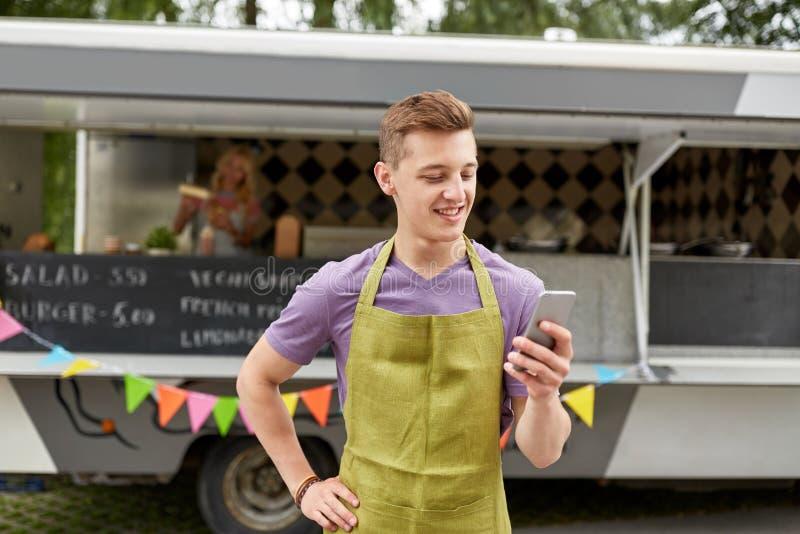围裙的推销员与在食物卡车的智能手机 免版税库存照片