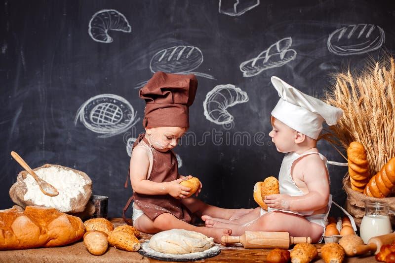围裙的迷人的矮小的小孩在桌上用面包 免版税库存照片