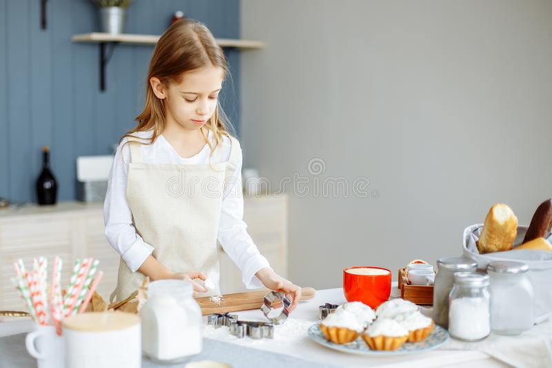 围裙的逗人喜爱的小女孩在厨房里烹调曲奇饼 库存图片