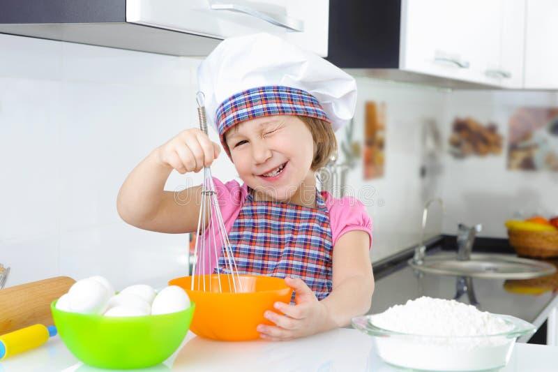 围裙的逗人喜爱的小女孩烹调曲奇饼的 库存图片