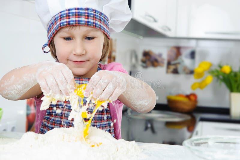 围裙的逗人喜爱的小女孩烹调曲奇饼的 图库摄影