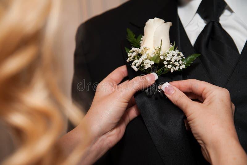 固定妇女的钮扣眼上插的花 库存图片