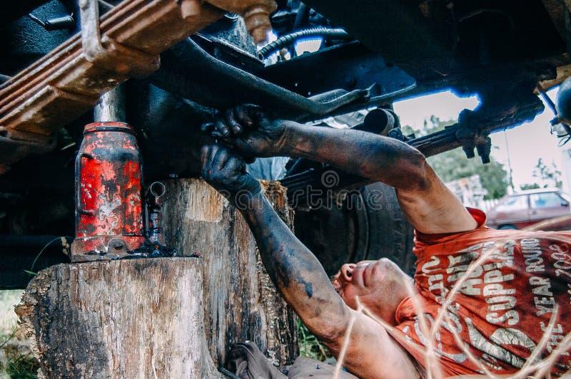 固定汽车的技工外面用肮脏的手 免版税库存图片