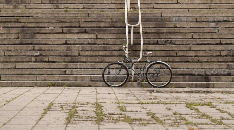 固定的站立在老都市葡萄酒街道上的齿轮黑色减速火箭的样式自行车反对台阶背景 免版税库存图片