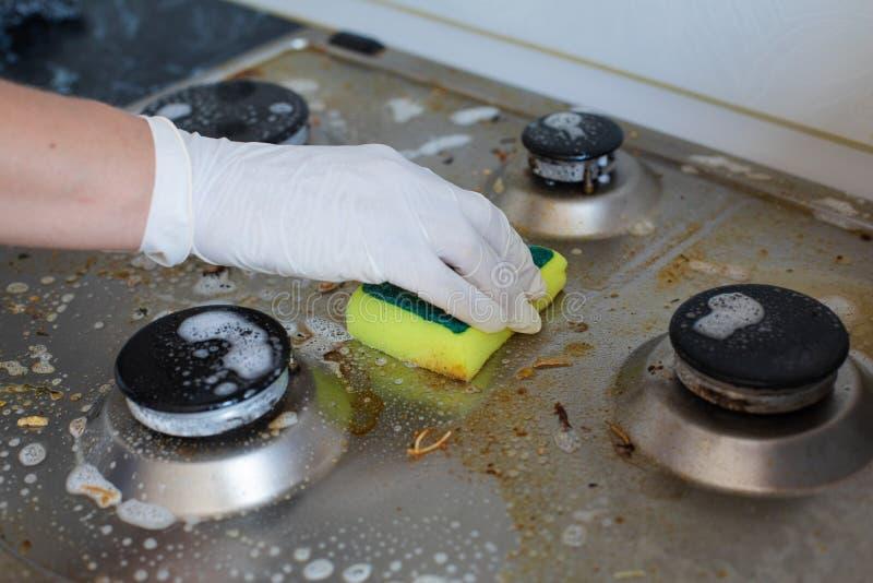 国内女性清洗肮脏的火炉的手佩带的手套在烹调以后使用洗涤的海绵 免版税库存图片