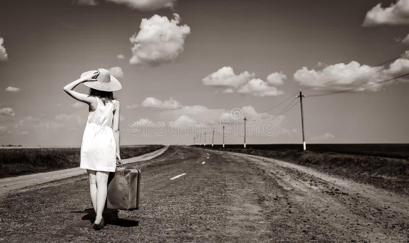 国家(地区)女孩偏僻的路手提箱 库存图片