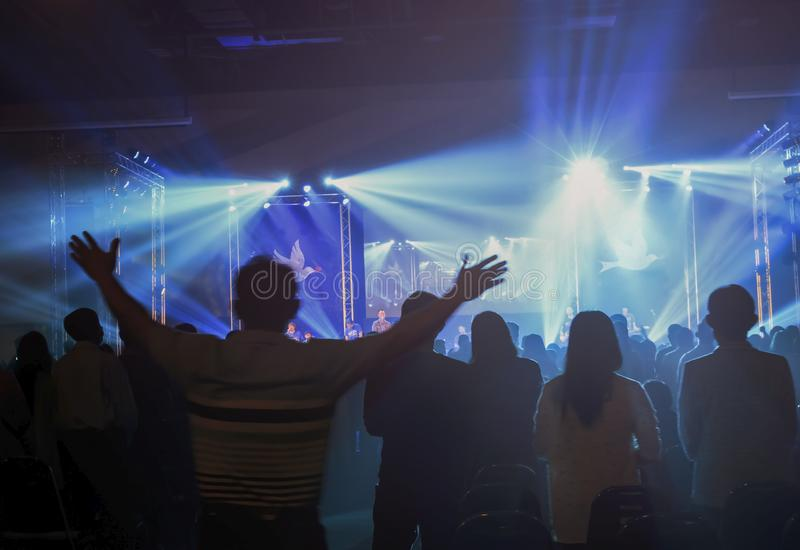 国际人的团结天概念:被弄脏的基督徒会众崇拜上帝一起在音乐s前面的教会大厅里 免版税库存照片
