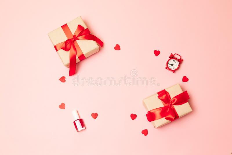 国际妇女节3月8日,情人节 惊奇有一把红色丝带弓、指甲油和一个红色时钟的礼物盒在a 免版税库存图片