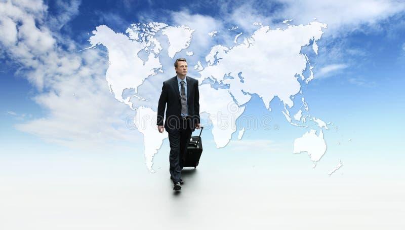 国际旅行商人、成功概念走与台车和公文包,在蓝天有地图背景 免版税库存照片