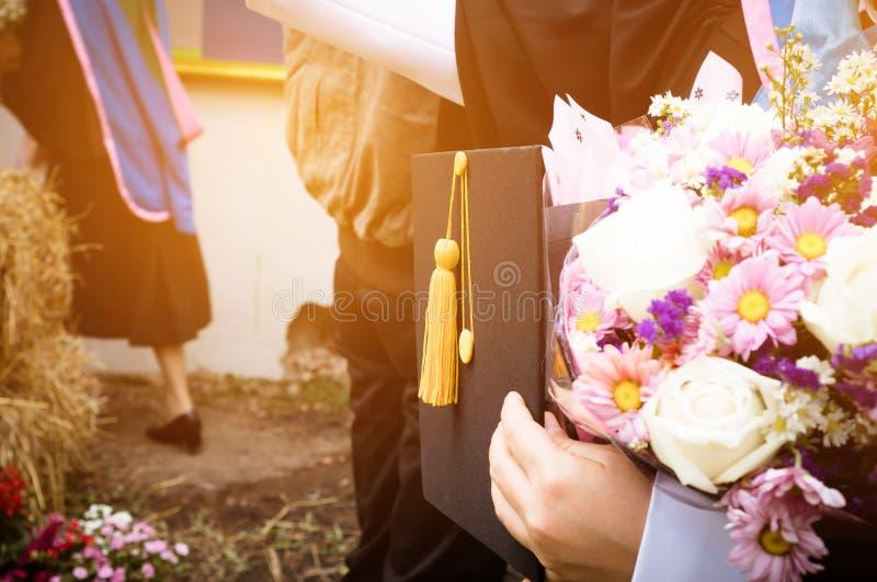 国际毕业生研究概念:毕业在学生妇女手上的黑色盖帽有花的在毕业典礼举行日在大学 免版税库存图片