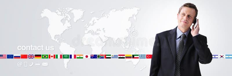 国际联络我们概念、商人与在世界地图背景隔绝的手机,旗子象和联络标志 库存图片