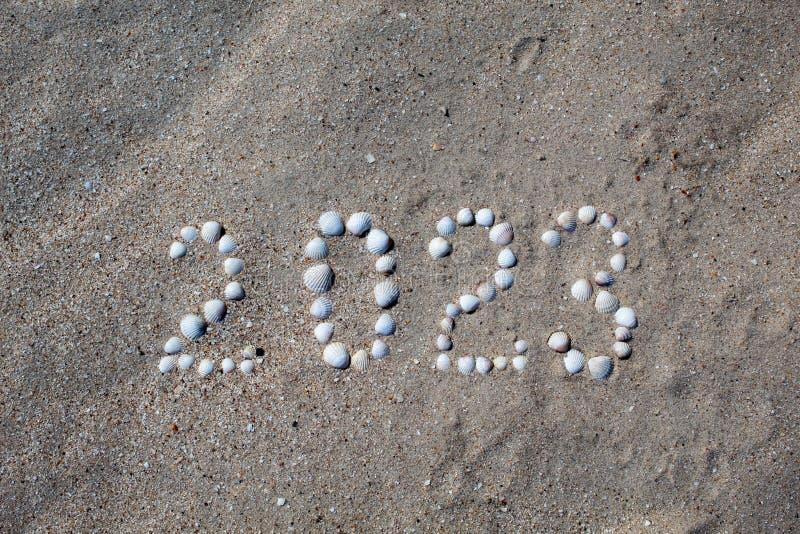 图'2023年'被计划在与壳的沙子上 免版税库存图片