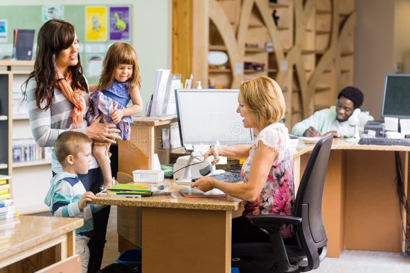 图书管理员在图书馆柜台的扫描书 免版税库存图片