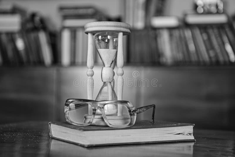 图书管理员归因于概念 计数时间的滴漏在古板的镜片附近 跌倒里面的沙子 免版税库存照片