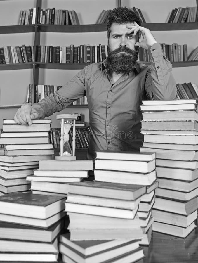 图书管理员概念 周道的面孔的人站立在堆书之间,当学习在图书馆里,书架时 库存照片