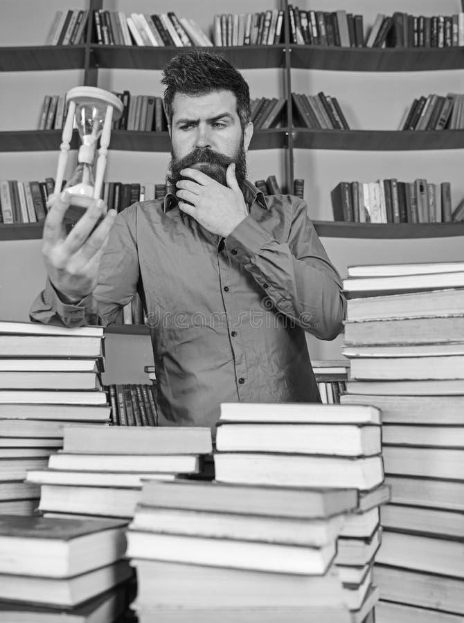 图书管理员概念 周道的面孔的人站立在堆书之间,而举行滴漏,书架  图库摄影