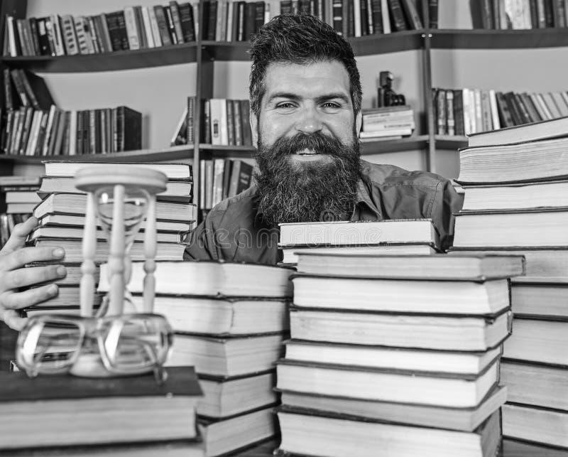 图书管理员概念 老师或学生有胡子的坐在桌上与书, defocused 愉快的面孔的人在堆之间  免版税图库摄影
