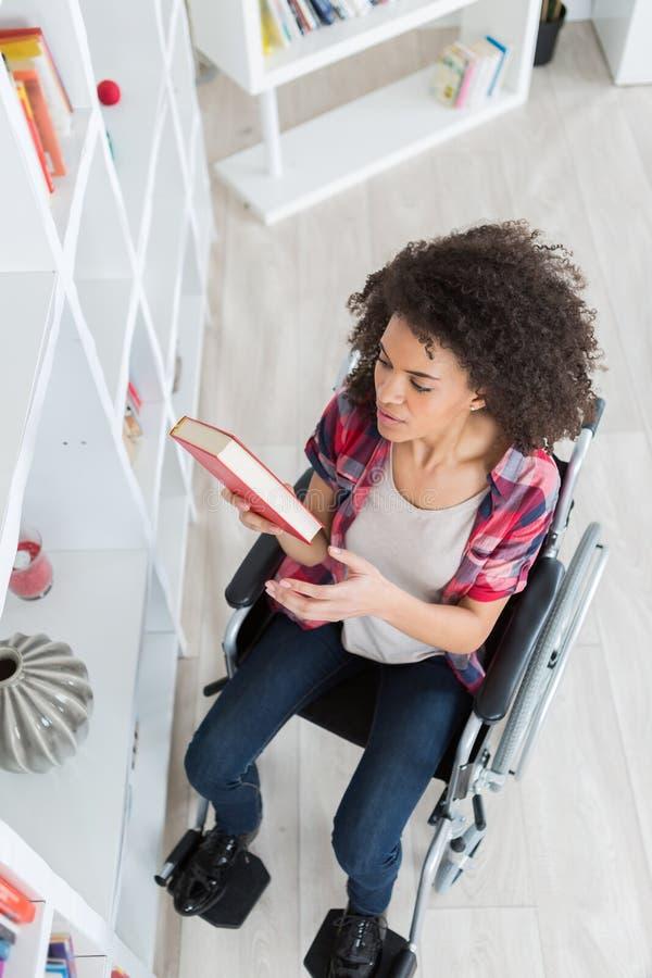 图书馆采摘书的残疾学生在大学 库存照片