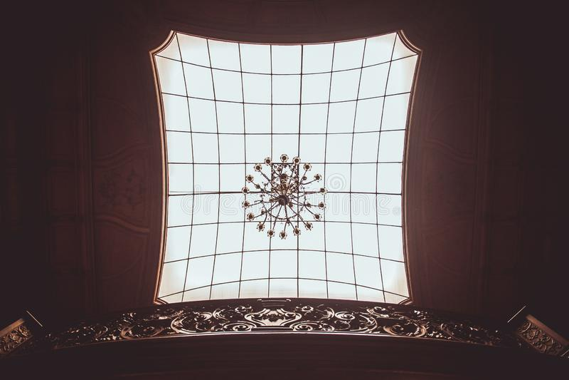 图天花板在屋子的大厅里有一盏大格子玻璃和昂贵的美丽的枝形吊灯的 方形的室内纹理 免版税库存图片