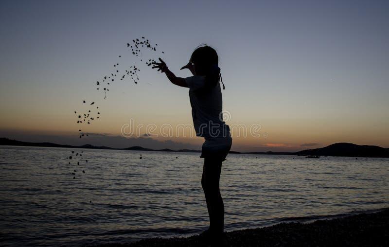 图投掷的石头在日落的海滩 免版税库存图片