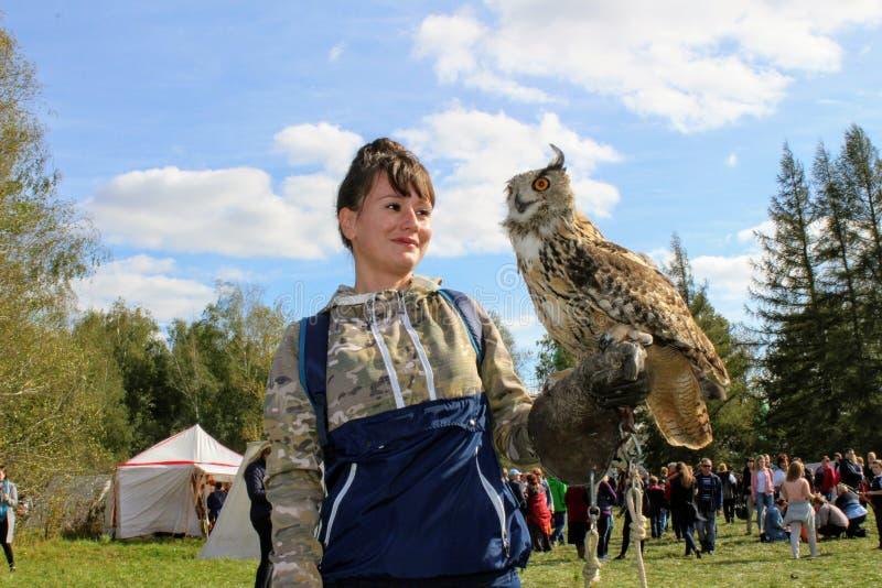 图拉9月, 16 2017年,俄罗斯-历史节日` Kulikovo领域` :有手套的一名妇女拿着在被伸出的手上的一头猫头鹰 图库摄影