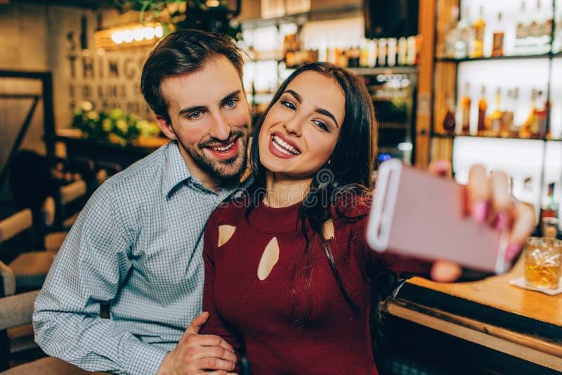 图片女孩做与她的boyfirend的地方selfie 他们是微笑和看对照相机 这对夫妇是 免版税库存图片