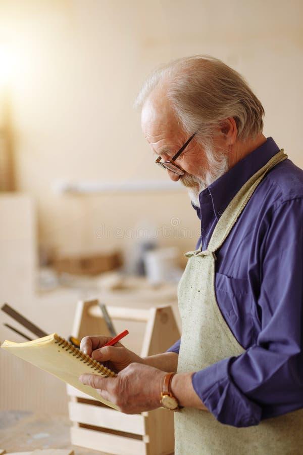 图画要素自然徒手画风格化 线描老木匠做着图画 库存照片