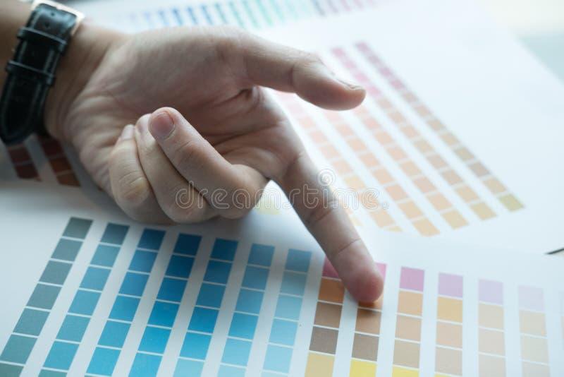 年轻图表设计师与颜色样片一起使用在现代offic 免版税图库摄影