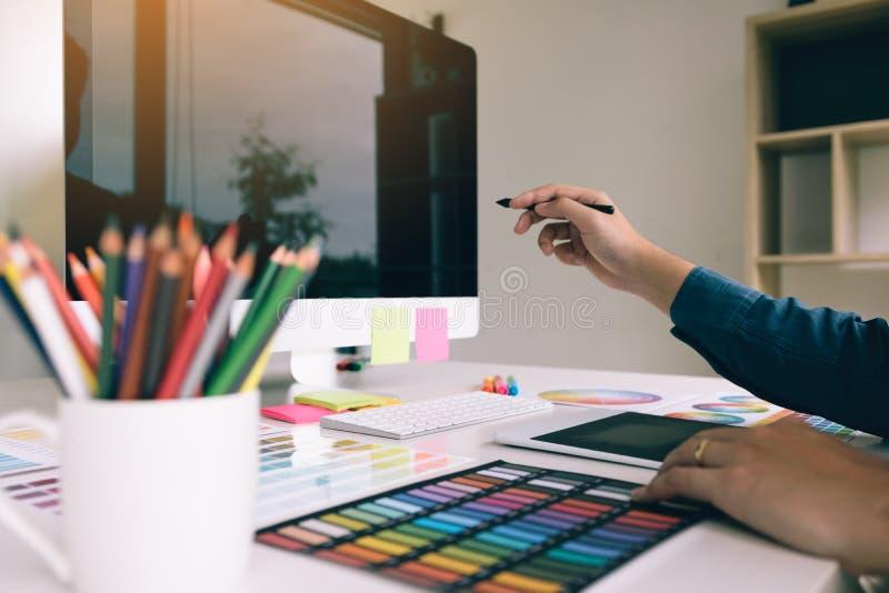 图表设计师把计算机指向的候宰栏工作场所 图库摄影