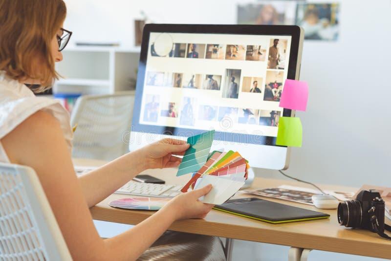 图表设计师检查颜色与颜色样片在书桌 库存照片